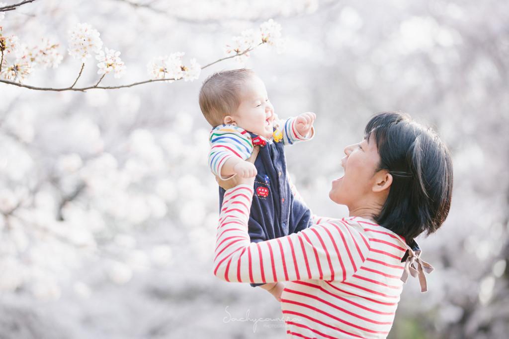 桜をバックに赤ちゃんを抱き上げるママ
