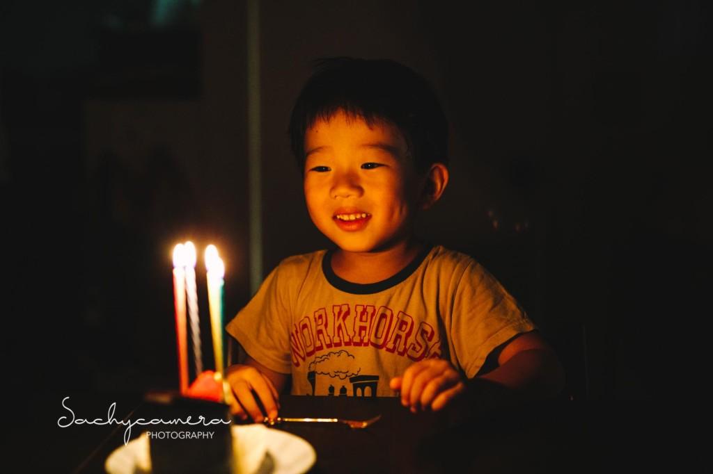 誕生日ケーキのロウソクを見つめている