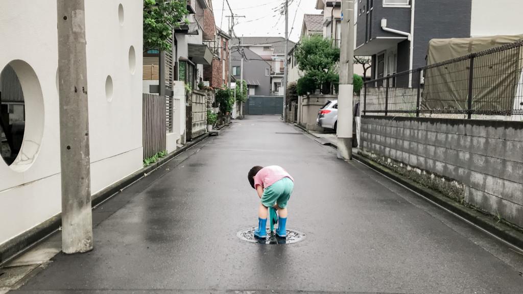 マンホールの穴に傘を突っ込む男の子